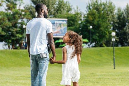 Photo pour Vue arrière du policier afro-américain et sa fille main dans la main et marcher dans le parc d'attractions - image libre de droit