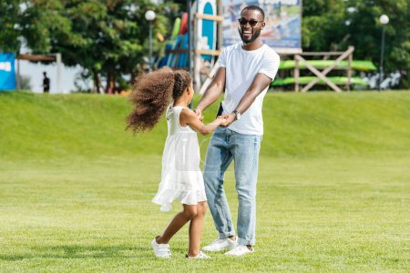 Photo for Happy african american father and daughter holding hands and spinning around in amusement park - Royalty Free Image