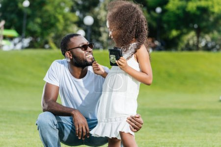 african american daughter standing with police badge and touching father beard in park