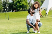 african american daughter standing with father police badge in park