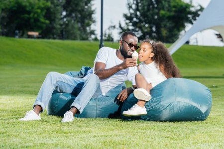 Photo for African american father giving ice cream to daughter on beanbag chairs in park - Royalty Free Image
