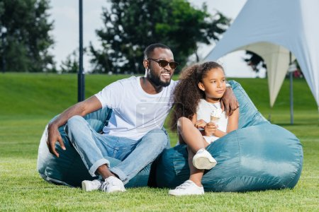 african american father and daughter with ice cream sitting on beanbag chairs in park and looking away