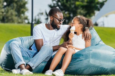 smiling african american father and daughter with ice cream looking at each others on beanbag chairs in park