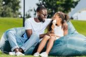 """Постер, картина, фотообои """"улыбаясь афро-американский отец и дочь с мороженым, глядя на друг друга на beanbag стулья в парке"""""""