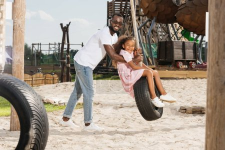african american father and daughter on tire swing at amusement park