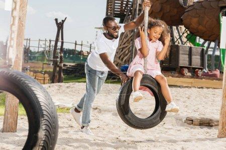 père afro-américain et sa fille sur la balançoire pneu s'amuser sur l'aire de jeux