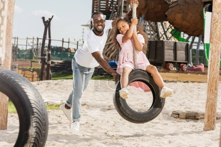happy african american father pushing daughter on tire swing at amusement park