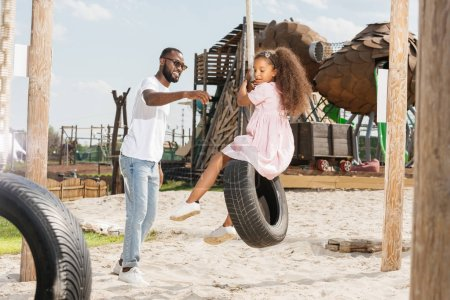african american father catching daughter on tire swing at amusement park