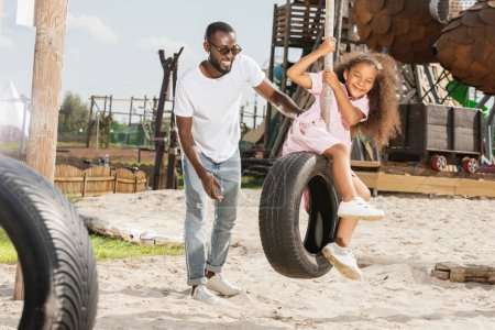 smiling african american father standing near daughter on tire swing at amusement park