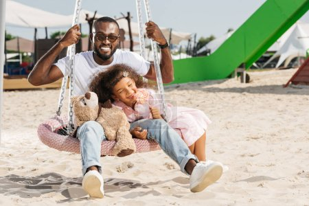 smiling african american father and daughter on spider web nest swing at amusement park