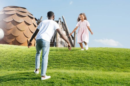 african american daughter running to father on hill at amusement park