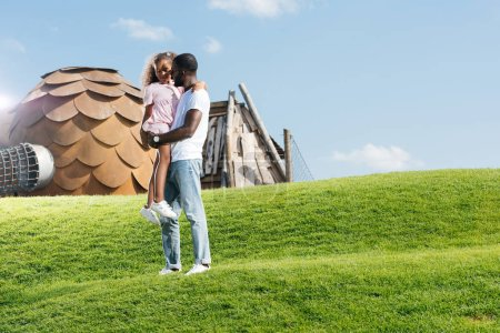 Photo for African american father holding daughter on hill at amusement park - Royalty Free Image