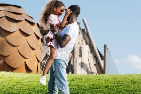 père afro-américain tenant fille heureuse sur la colline verte au parc d'attractions
