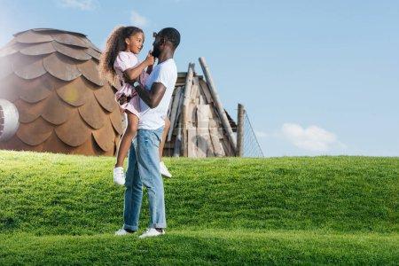 père afro-américain tenant fille souriante sur la colline verte au parc d'attractions