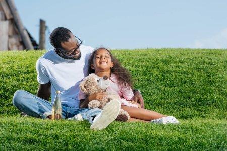 père afro-américain et fille souriante assis sur la colline avec soda et ours en peluche au parc d'attractions