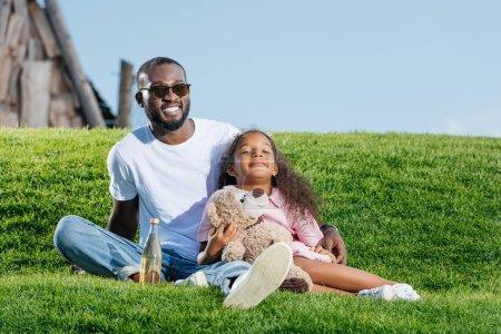 heureux père afro-américain et sa fille assis sur la colline avec soda et ours en peluche au parc d'attractions