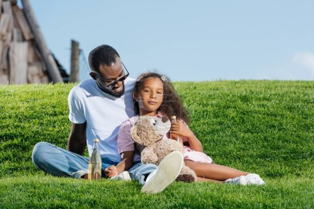 Photo for African american father and daughter sitting on hill with soda and teddy bear at amusement park - Royalty Free Image