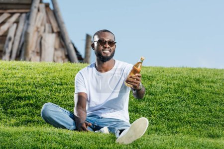 handsome african american man sitting on green hill and holding soda in glass bottle