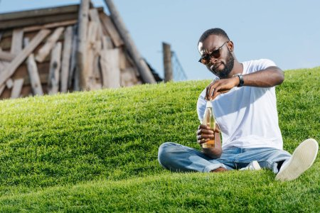 handsome african american man opening soda bottle on green hill