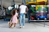 rear view of african american policeman walking with daughter and holding police badge at amusement park