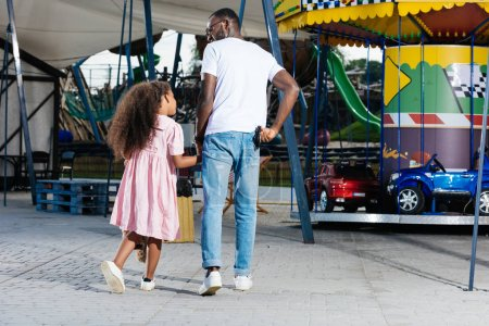 back view of african american police officer walking with daughter and holding police badge at amusement park