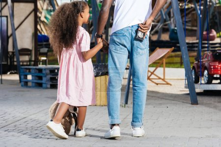 cropped image of african american police officer walking with daughter and holding police badge at amusement park