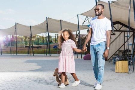 Foto de Sonrisa de padre afro americano y su hija tomados de la mano y caminando en el parque de atracciones - Imagen libre de derechos