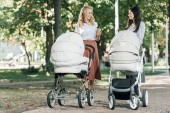mothers holding coffee to go and walking with baby strollers in park