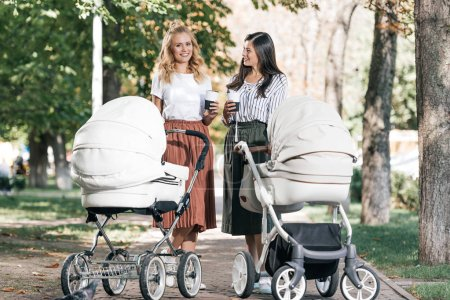 Photo for Smiling mothers holding coffee to go and walking with baby strollers in park - Royalty Free Image