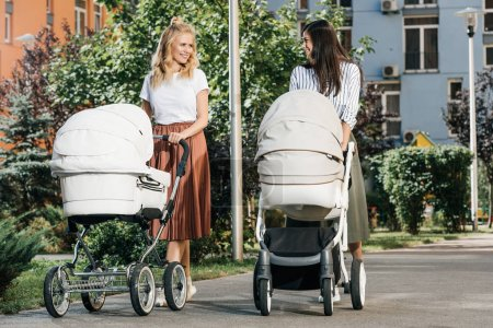 mothers walking with baby strollers on street