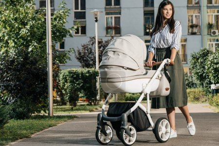 Photo for Attractive mother walking with baby stroller on street and looking away - Royalty Free Image