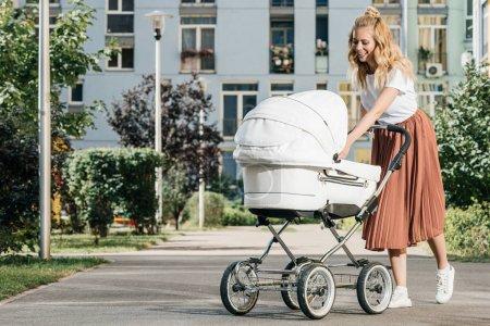 Foto de Madre caminando y mirando el cochecito de bebé en la calle - Imagen libre de derechos