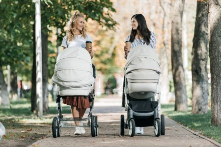 Photo for Mothers walking with baby strollers and coffee to go in park and looking at each other - Royalty Free Image