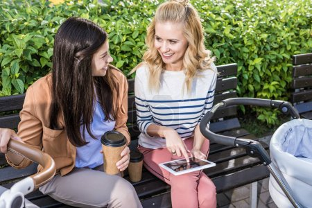 Photo for Smiling mothers sitting on bench near baby strollers with coffee to go and tablet - Royalty Free Image