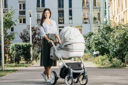 mother standing on street with baby stroller and looking away