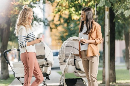 Photo for Mothers talking, standing with coffee to go and baby strollers in park - Royalty Free Image