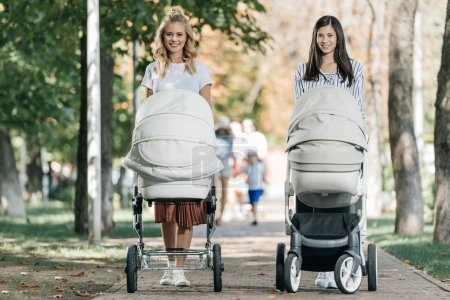 Photo for Smiling mothers walking with baby strollers in park and looking at camera - Royalty Free Image