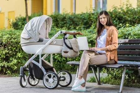 freelancer working with laptop on bench near baby stroller in park