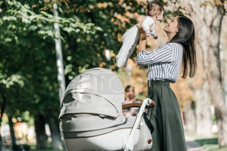happy mother holding baby near stroller in park
