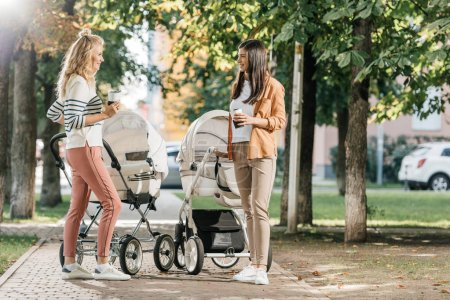Photo for Mothers standing with coffee to go near baby strollers in park - Royalty Free Image
