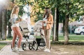 mothers standing with coffee to go near baby strollers in park