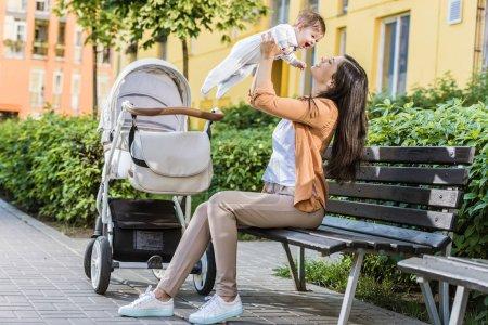 vue de côté de mère tenue bébé heureux sur le banc près de poussette