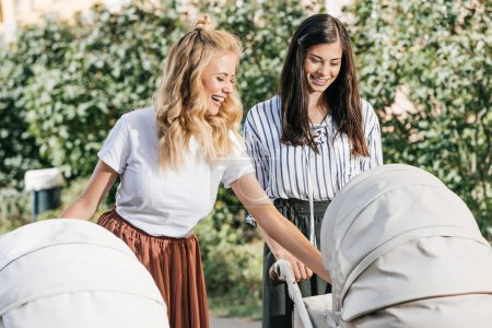Photo for Happy mothers looking at baby carriages in park - Royalty Free Image