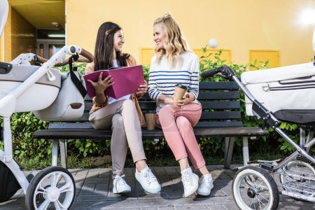 mothers sitting on bench near baby strollers with folder and coffee in paper cup