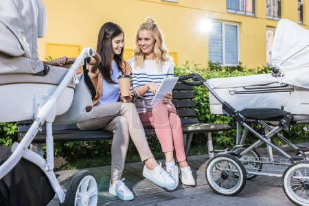 Photo for Smiling mothers sitting on bench near baby strollers with coffee to go and looking at tablet - Royalty Free Image