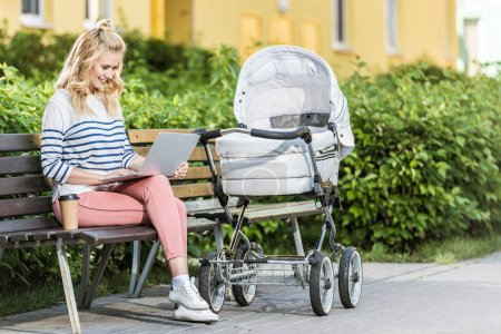Photo for Smiling freelancer working with laptop on bench near baby stroller in park - Royalty Free Image