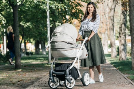 beautiful mother walking with baby stroller in park and looking at camera