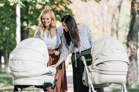 smiling mothers looking in baby stroller in park