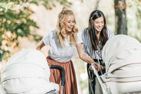 laughing mothers looking in baby stroller in park