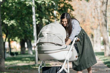 attractive happy mother looking in baby stroller in park